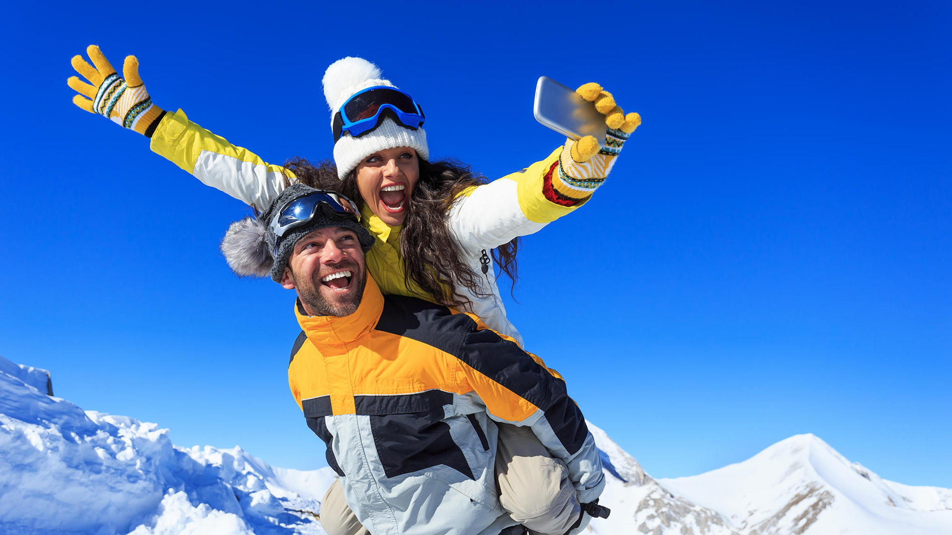 Man and woman taking selfie on top of snowy mountain