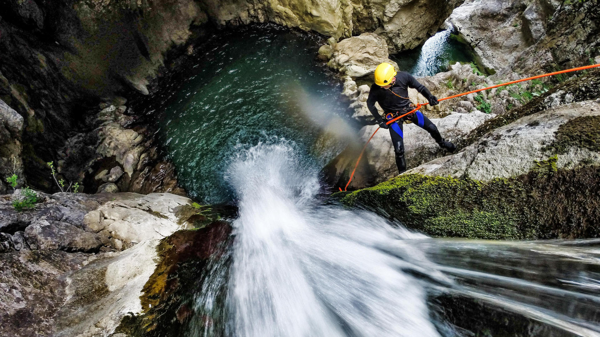 Man wearing helmet abseiling from waterfall