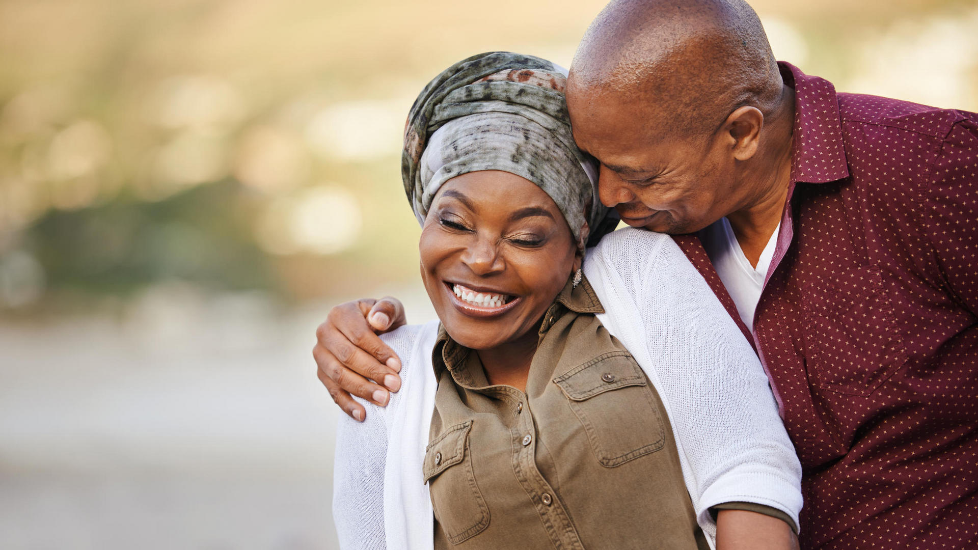 Elderly couple hugging and smiling