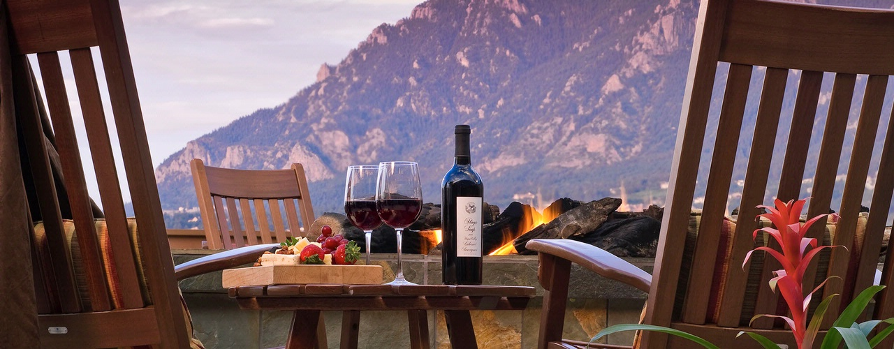 2 glasses of wine and cheese board with mountains in the background