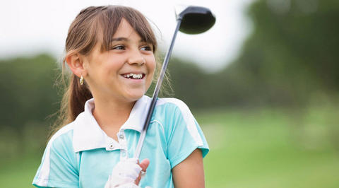 Young girl holding a golf driver and smiling