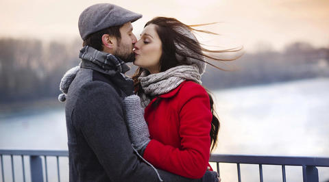 Man and woman kissing on bridge in winter