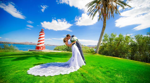 Man and woman kissing in front of red and white striped lighthouse