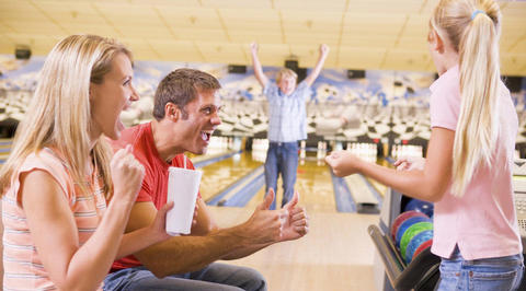 Father and children celebrating while bowling