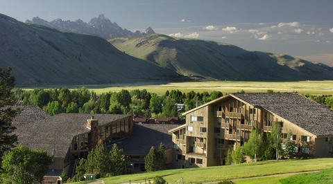 Luxury mountain lodging in front of green mountain range