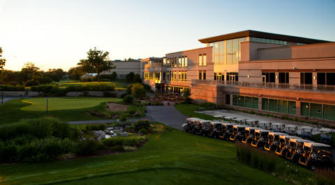 Exterior of golf club house with golf carts parked outside