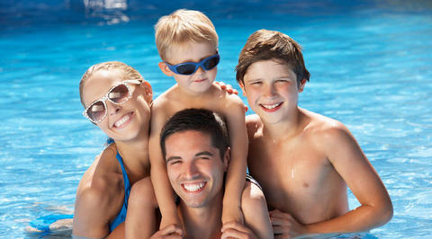 Family of 4 smiling in the swimming pool