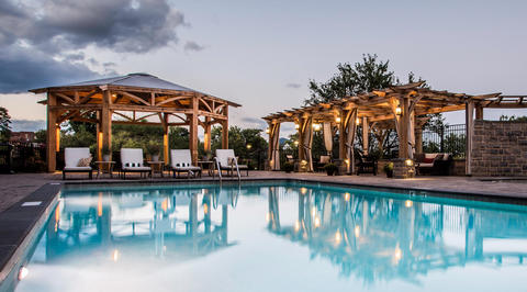 Outdoor swimming area with bright lit cabanas
