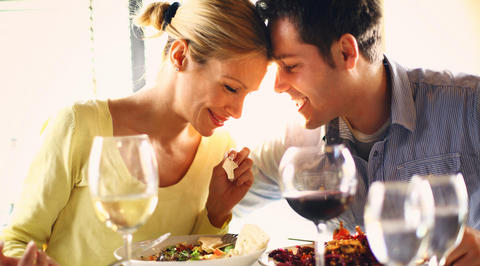 Man and woman touching foreheads while eating dinner together