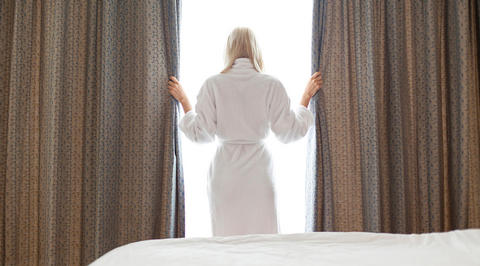 Woman wearing bathrobe looking out of hotel window