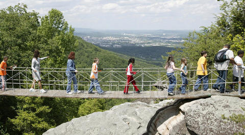 Group of people crossing bridge above Smoky Mountains
