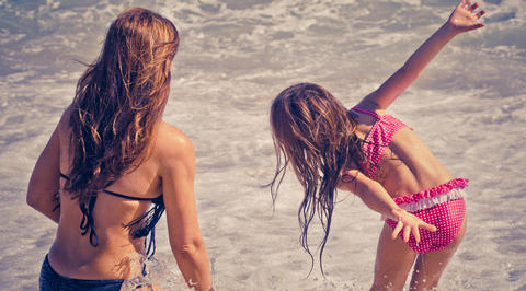 Mother and daughter playing in shallow ocean water