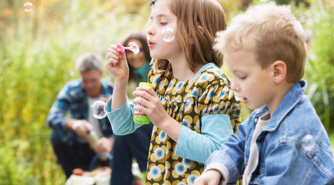 Girl blowing bubbles with her family