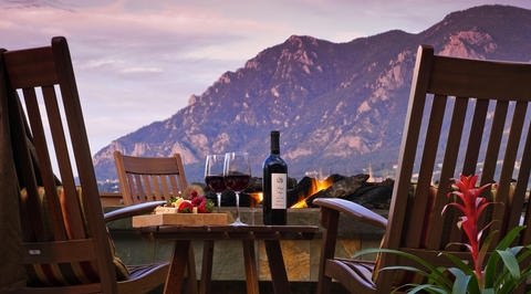 2 glasses of red wine and cheeseboard with mountains in background