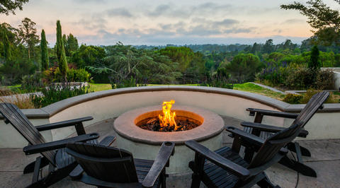 Outdoor seating area with fire pit overlooking green woodlands