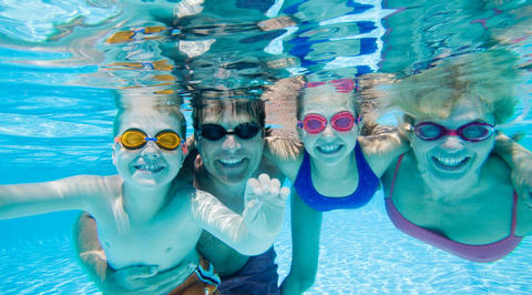 Family of 4 smiling in the pool underwater