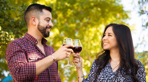 Man and woman raising glasses of red wine