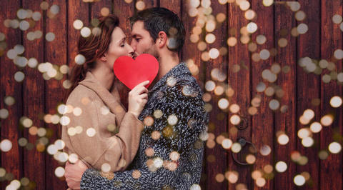 Man and woman kissing, holding love heart in front of faces