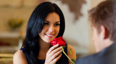 Woman smelling red rose while smiling at man