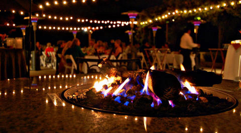 Outdoor restaurant seating area with flaming fire pit