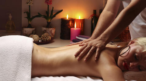 Woman receiving back massage in spa